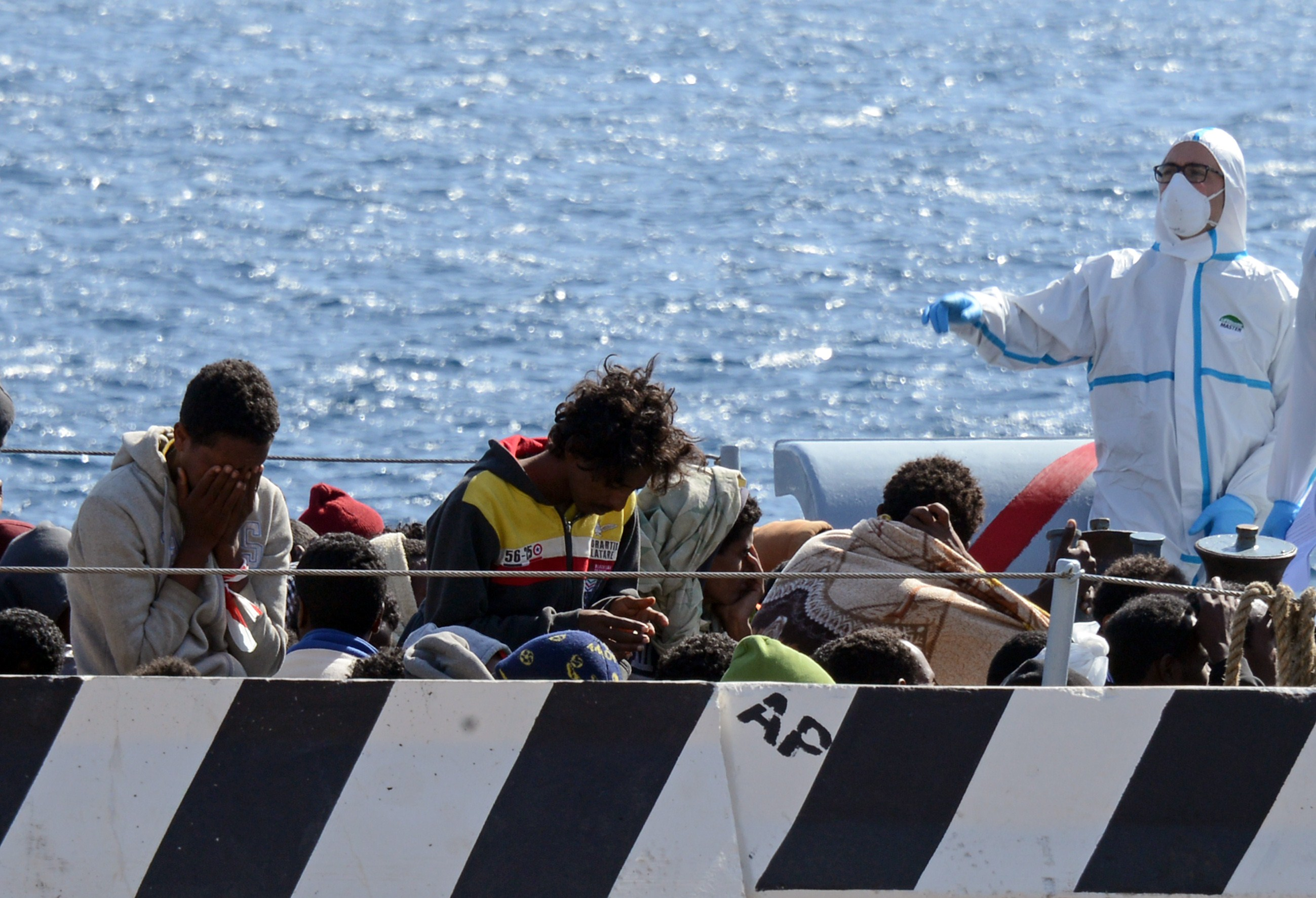 Migrants arrive in the port of Messina after a rescue operation at see on April 18, 2015 in Sicily. A surge of migrants pouring into Europe from across the Mediterranean won't end before chaos in Libya is controlled, Italy's prime minister said yesterday, as the Vatican condemned a deadly clash between Muslim and Christian refugees on one boat. Italian authorities have rescued more than 11,000 migrants making the often deadly voyage from North Africa in the past six days, with hundreds more expected, the coastguard said.  AFP PHOTO / GIOVANNI ISOLINO        (Photo credit should read GIOVANNI ISOLINO/AFP/Getty Images)