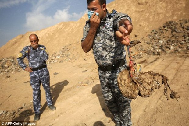 A member of the Iraqi forces holds a skull they dug up from the mass grave