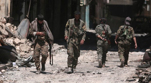 Syria Democratic Forces (SDF) fighters walk on the rubble of damaged shops and buildings in the city of Manbij, in Aleppo Governorate, Syria, August 10, 2016. © Rodi Said / Reuters