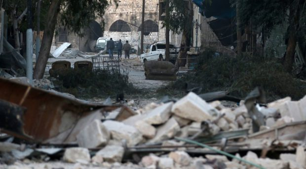 People walk near rubble of damaged buildings, in the rebel-held besieged area of Aleppo, Syria November 19, 2016. © Abdalrhman Ismail / Reuters