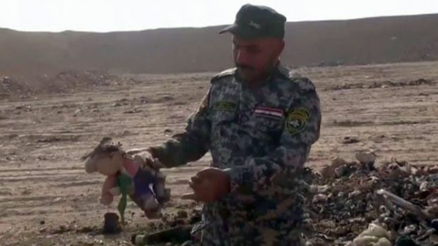 Video footage showed a soldier holding up a child's stuffed toy found at the grave