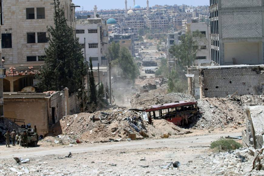 Forces loyal to Syria's President Bashar Assad stand near barricades after they advanced on the southern side of the Castello road in Aleppo, Syria, Thursday. | SANA / HANDOUT VIA REUTERS