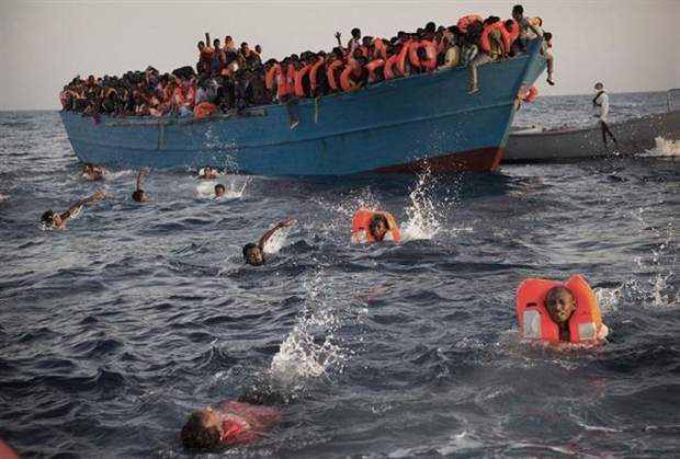 In this Aug. 29, 2016 file photo, migrants, most from Eritrea, jump into the water from a crowded wooden boat as they are helped by members of a nongovernmental organization during a rescue operation in the Mediterranean Sea, about 13 miles (20 kilometers) north of Sabratha, Libya. A new EU report accessed by The Associated Press on Thursday, Dec. 1, 2016, says that Libya's coastal cities are generating up to 325 million euros ($346 million) in revenue each year from people smuggling. (AP Photo/Emilio Morenatti, File)
