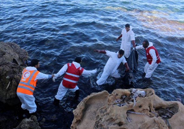 Rescue workers recover the body of a migrant on a beach in the coastal town of Tajoura, east of Tripoli Sunday. | REUTERS