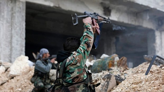 Syrian army soldiers fire their weapons during a battle with rebel fighters in east of Aleppo on Monday. Russia and China vetoed a UN resolution for a seven-day truce in the city, with Russia arguing it would allow rebels to regroup. (Hassan Ammar/Associated Press)