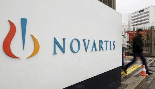 A man walks past the logo of Swiss drugmaker Novartis AG in front of a plant in Basel. REUTERS/Arnd Wiegmann/Files
